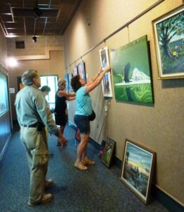 Butch, Ruth, Cathy, and Shirley hanging the Acrylic section.